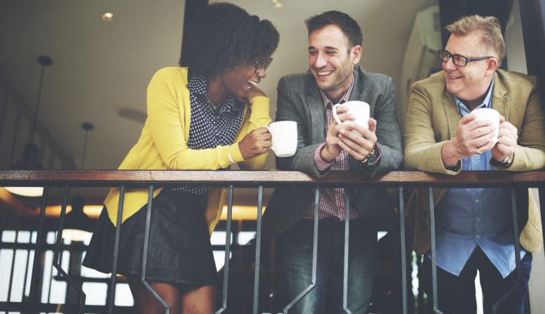 Tre glada människor skrattar och samtalar över en kopp kaffe