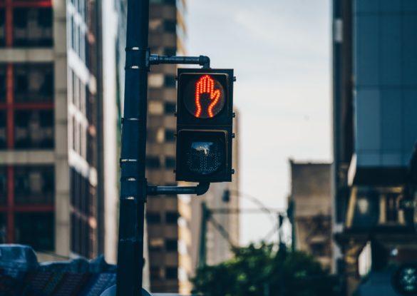 Röd gubbe på trafikstolpe